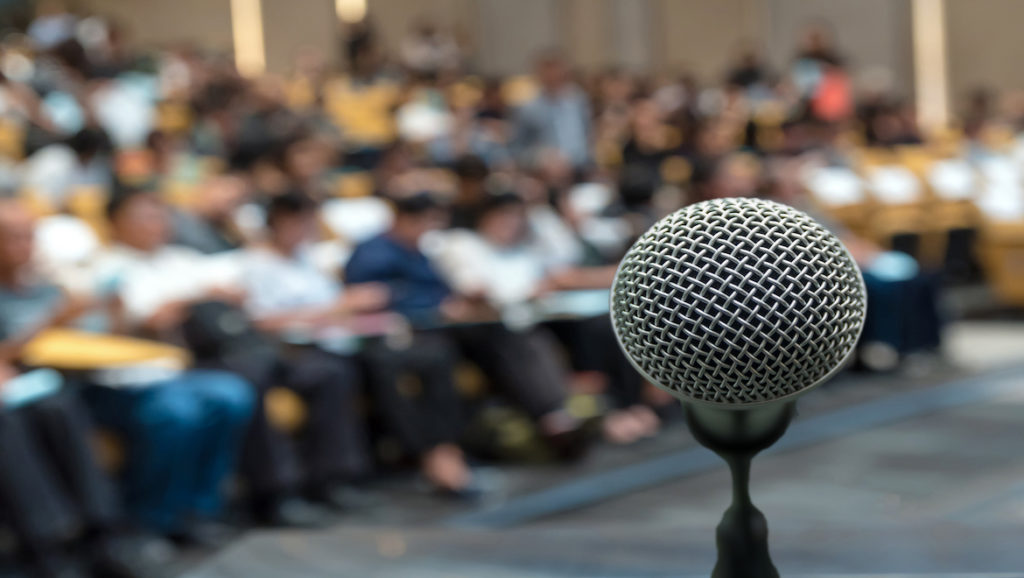 Point of view perspective of microphone on stage at a public speaking event with seated audience