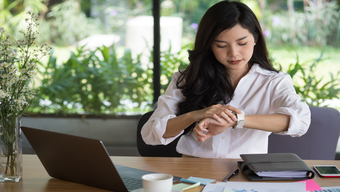 entrepreneur woman in office at work, sitting in at desk, looking at her watch