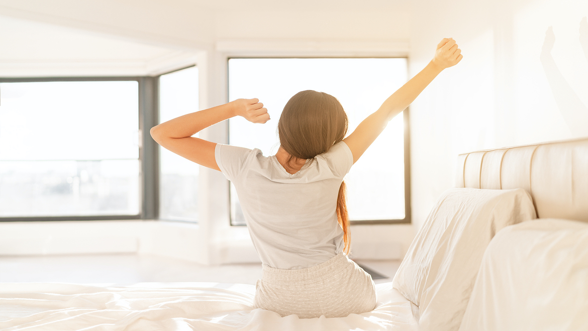 Woman sitting on the bed stretching after waking an hour earlier
