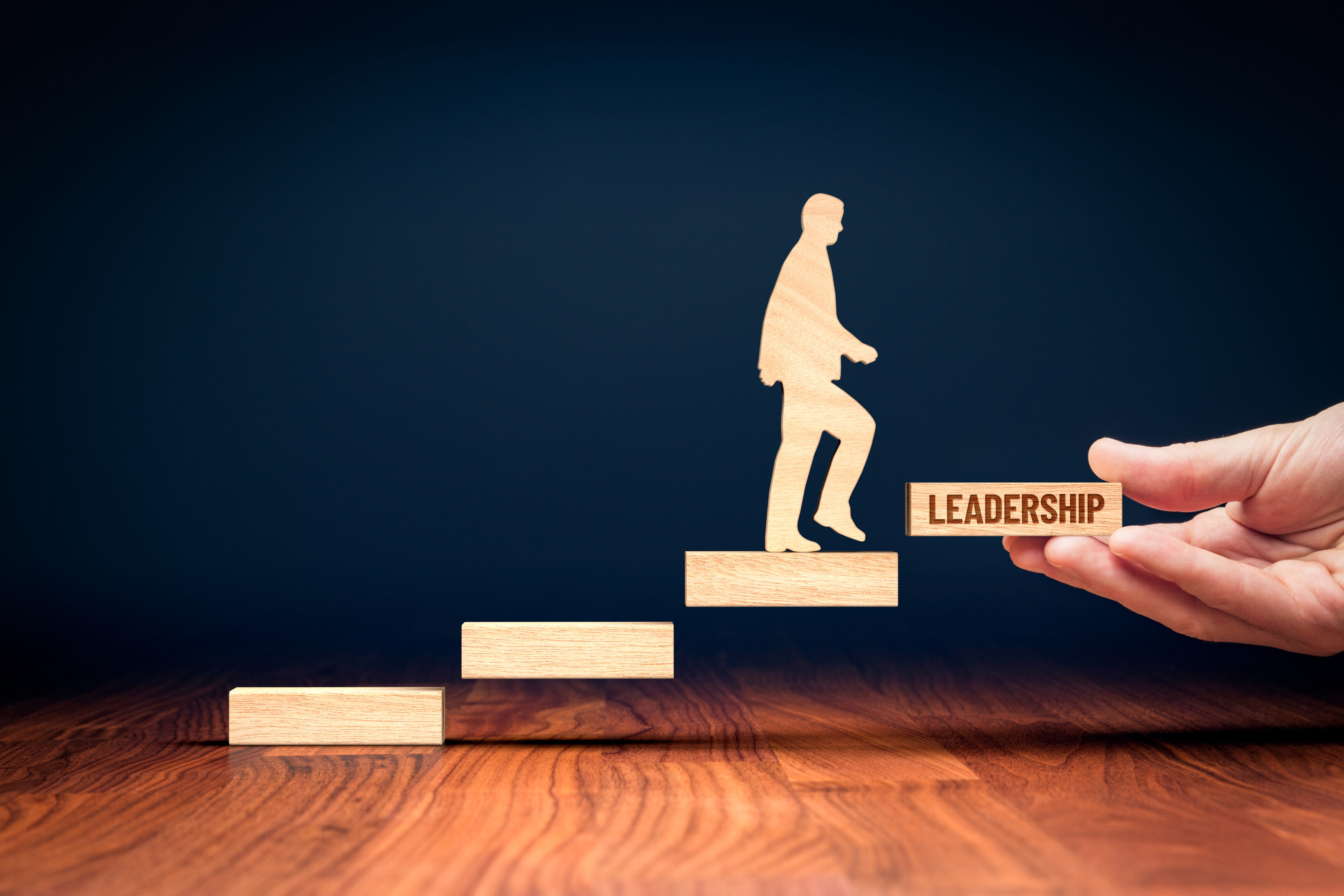 """Leader going up wooden steps towards a final step labeled """"leadership."""""""